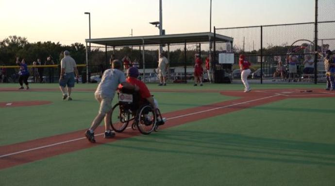 Miracle Field of the Quad Cities - Man pushing man on wheelchair around baseball diamond